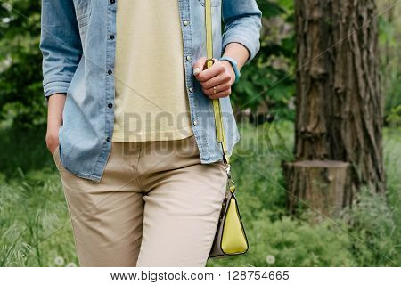 Woman in denim shirt and a yellow T-shirt and pants walking on the green park in spring