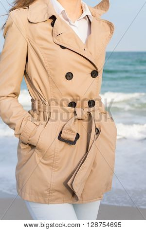Slender girl in a beige coat and jeans walking along the beach in the evening sun