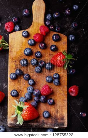 Organic blueberries served in the vintage cutting board over a black slate board and dark metal background. Dark Rustic Style. Concept Healthy Food