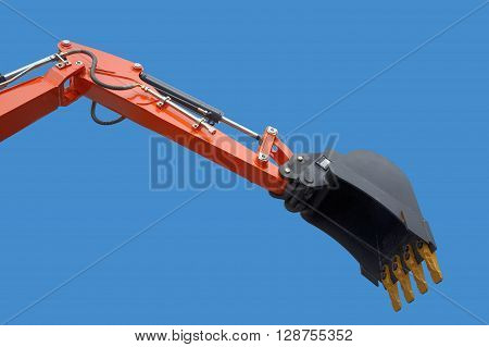 New excavator bucket on blue sky. Hydraulics.