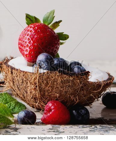 Organic berries: blueberries and strawberries served in two coconuts on a light wooden rustic, background. Concept of healthy food. Top view. Selective Focus ** Note: Soft Focus at 100%, best at smaller sizes