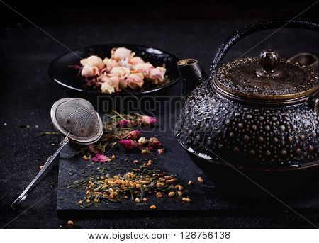 Tranditional eastern metal teapot with the variety of tea, infused with herbs and flowers over the black stone slate board
