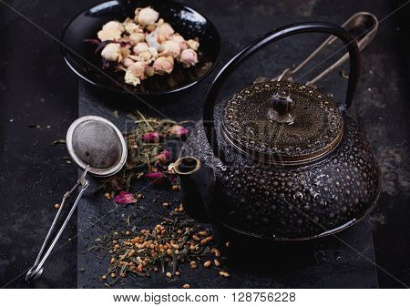 Tranditional eastern metal teapot with the variety of tea, infused with herbs and flowers with baboo mat and chop stickst over the black stone slate board