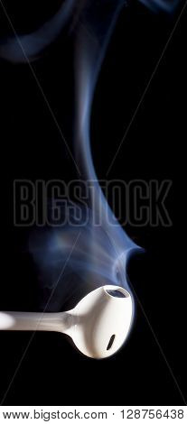 Smoke rising from a pair of white ear buds on a black background