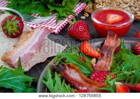 Useful strawberry salad with arugula nuts and fried bacon