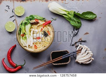Japanese  bowl of ramen soup with tofu cheese, noodles, bok choi, smimeji  seaweed, chili, and lime  served with turquoise chopsticks over metal table. Dark rustic style. Top view