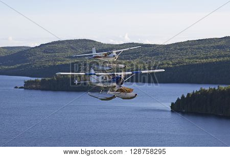 two beaver airplanes flying side to side over a wild lake