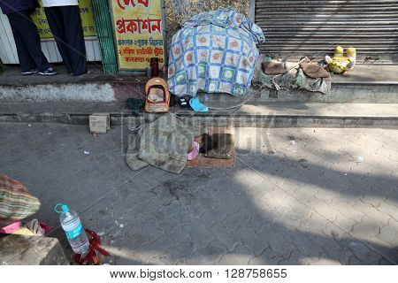 KOLKATA, WEST BENGAL, INDIA - FEBRUARY 12: A little Indian girl sleeping on the street, Kolkata, India on February 12, 2014.