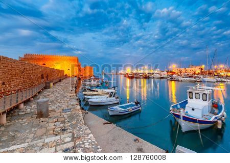 Old harbour of Heraklion with Venetian Koules Fortress, boats and marina during blue hour, Crete, Greece. Boats blurred motion on foreground.