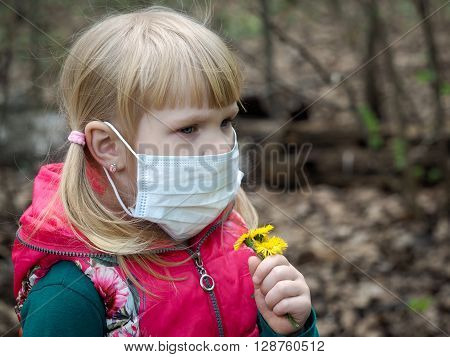 Girl with spring flowers and a medical mask. Early spring, the first flowers of a dandelion. The concept of allergy, pollen, spring bloom, ecology