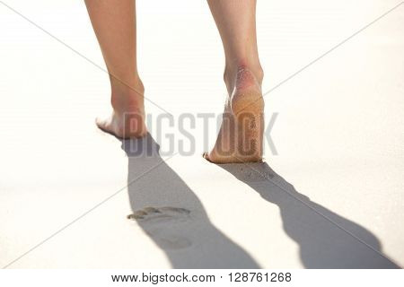 Woman Leaving Footprints In The Beach Sand