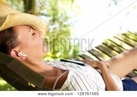 Woman Lying Down On Hammock Listening To Music