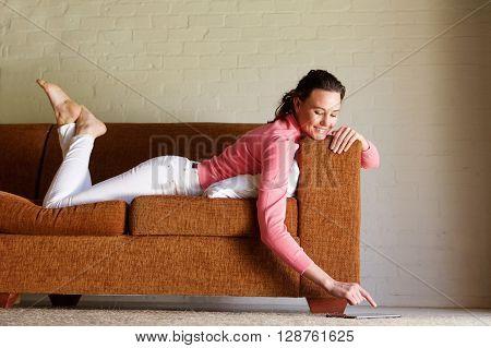 Young Woman Lying On Sofa Using Digital Tablet