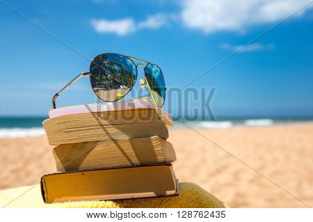 Books and sunglasses on a beach Maldives