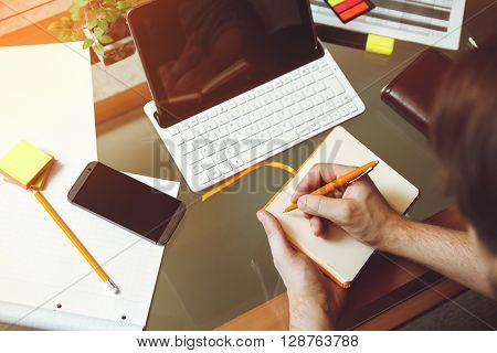 A man sitting at a desk, writing a pencil in a notebook. Mock up. Top view . Telework concept