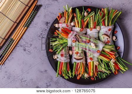 Spring rolls with vegetables and shiitake mushrooms on a plate top view.
