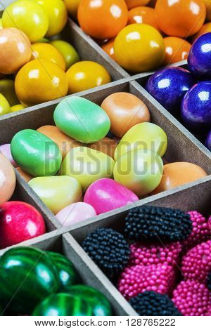 multi colored candy and chewing gum in a wooden box. Focus in the middle of the frame