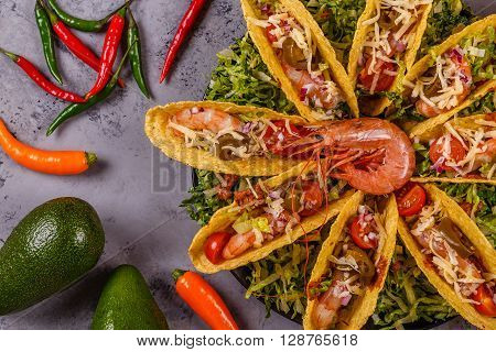 Tacos with shrimp lettuce cheese and jalapeno top view.