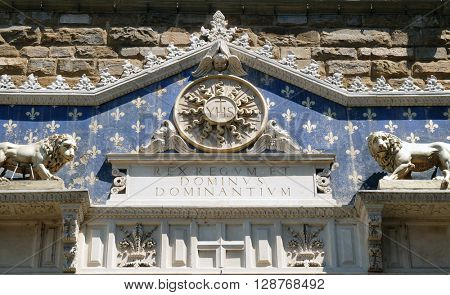 FLORENCE, ITALY - JUNE 05: Medallion with the IHS monogram between two lions, above to the entrance to Palazzo Vecchio, a UNESCO World Heritage Site in Florence, Italy, on June 05, 2015