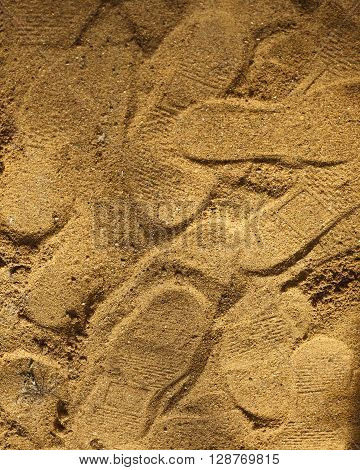 Many shoe footprints on the yellow sand