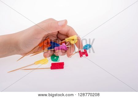 letters made of candles on sticks falling off hand