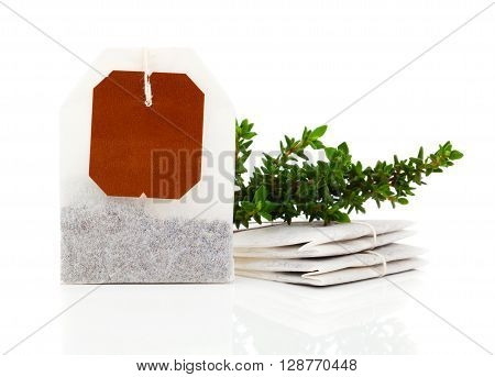 Teabag with green thyme herbs. Isolated on white background
