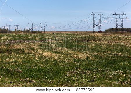 Electrical tower on a background of field with green grass