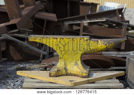 A huge yelow anvil on pallet on the ground