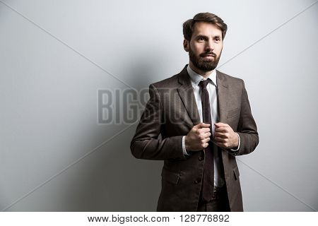 Businessperson in suit standing against light wall. Mock up
