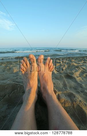Two Bare Feet Of A Tired Man On The Sandy Beach
