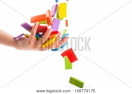 Falling colorful domino onto a hand on a white background