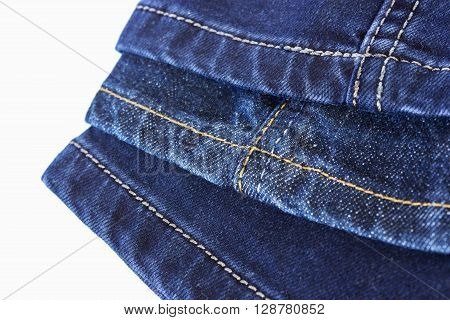 Various seams on blue denim trousers on a white background