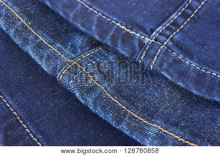 Seams on blue denim trousers on a white background