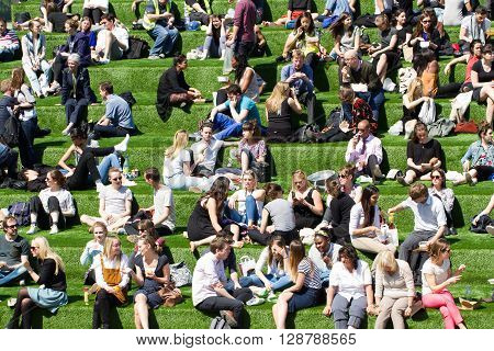 KINGS CROSS, LONDON, UK - MAY 5, 2016. Family, friends, colleagues and workmates taking a lunch break and enjoying the summer sunshine on a grassy hill in the heart of the city of London.