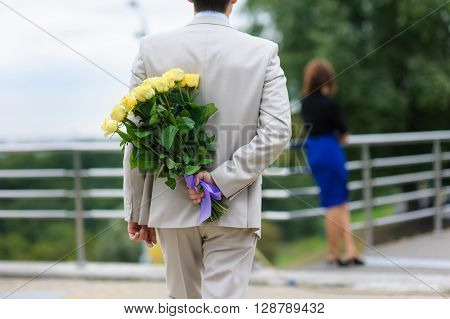 Young man hides a bouquet of flowers behind his back. Yellow roses in a man's hand. The man in a suit. The figure of a girl in the background.