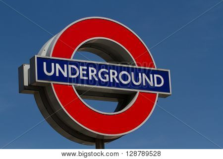 LONDON, UK - MAY 5, 2016. A London Underground sign marking the entrance to an underground train station in the city of London with a clear, blue sky behind.