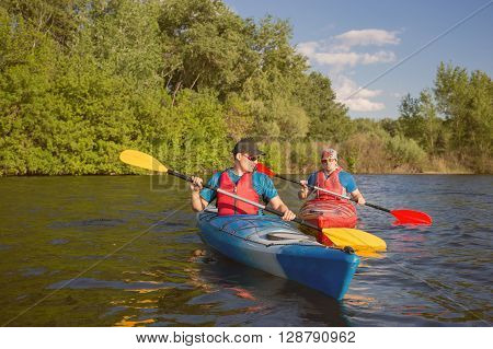 Mens travel by canoe on the river in the summer a sunny day.