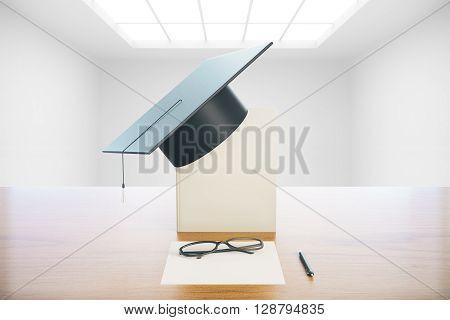 Graduation concept with book graduation cap glasses and paper on wooden desktop. Empty concrete interior background. 3D Rendering