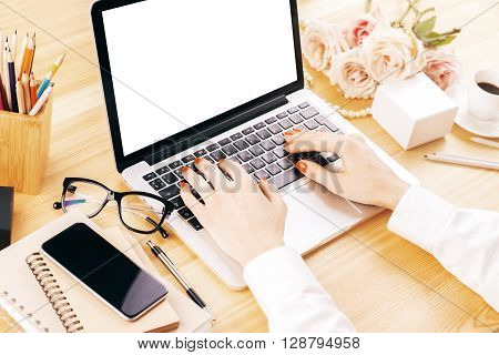 Business woman using laptop with blank white mock up screen on designer desktop. Rear view of business woman hands busy using laptop with copyspace screen. Mock up