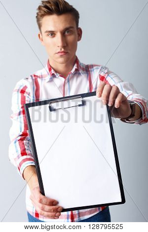Look at this document. Portrait of cheerful young man showing a folder to camera. He is standing and looking forward with seriousness. Isolated