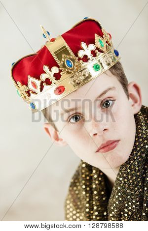 Serious Young Boy In Royal Gown And Crown
