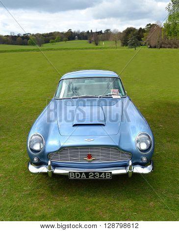 Saffron Walden, Essex, England - April 24, 2016: Classic Light Blue Aston Martin DB5 sports car parked on grass.