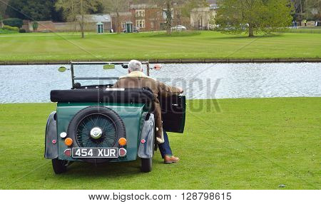 Saffron Walden, Essex, England - April 24, 2016: A Vintage Morris Minor motor car parked near water with driver.