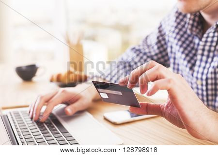 Online shopping and payment concept with caucasina male at desk typing on computer keyboard and holding a credit card
