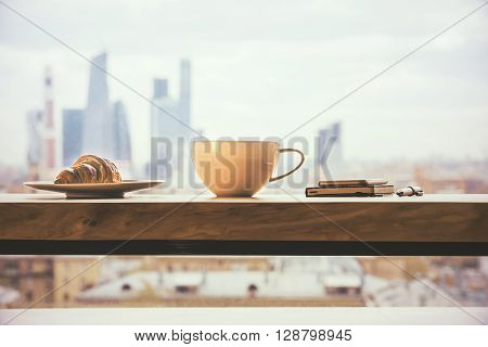 Closeup of round coffee mug croissant and phone with diary on wooden desktop and city background