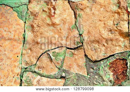 Old broken orange stone with deep green cracks. Stone rough textured background