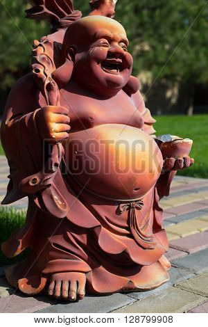 Chinese statuette, Smile fat buddha with money statue the symbol of wealthy isolated.