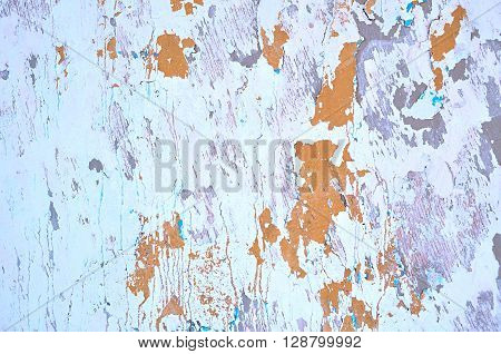 Textured grunge background - peeling light stucco and peeling brown paint with turquoise streaks on the aged texture wall surface. Architecture texture background