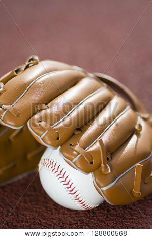 Baseball glove and ball on baseball field.