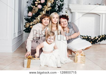 christmas, x-mas, winter, happiness concept - smiling happy family: grandmother, mother, daughter, granddaughter around the Christmas tree with gifts, 4 generations of the family, four, love concept